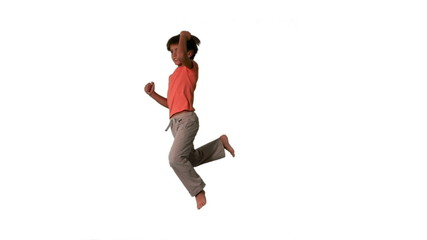 Side view of boy jumping up and down on white background