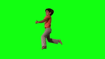 Side view of happy boy jumping up and down on green screen