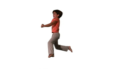 Side view of happy boy jumping up and down on white background