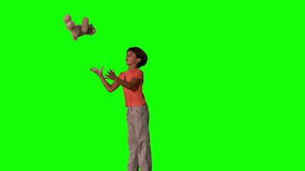 Side view of boy jumping and catching teddy on green screen