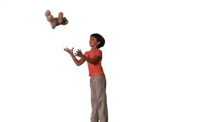 Side view of boy jumping and catching teddy on white background