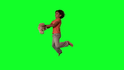 Side view of boy jumping up and catching teddy on green screen
