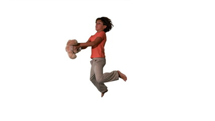 Side view of boy jumping up and catching teddy