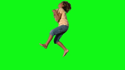 Boy jumping to catch teddy bear on green screen