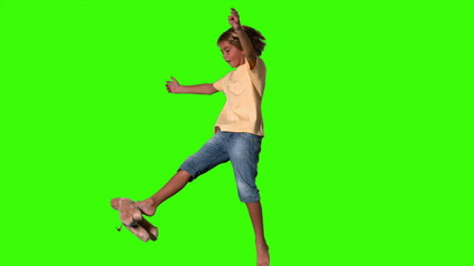 Boy jumping to kick teddy bear on green screen