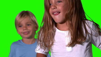 Cute siblings jumping together on green screen