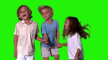 Siblings holding hands and jumping on green screen