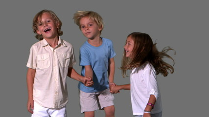 Siblings holding hands and jumping on grey background