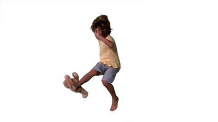 Little boy jumping up and kicking teddy on a white background