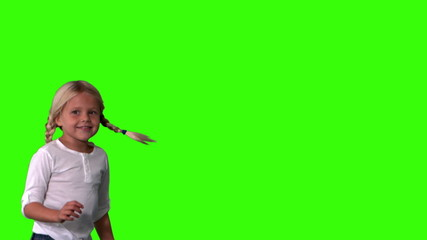 Cute girl in pigtails jumping on green screen