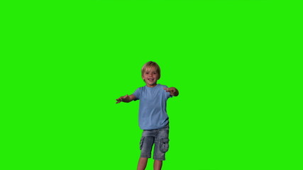 Boy in denim shorts jumping on green screen