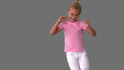 Joyful little girl jumping on grey background