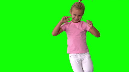 Joyful little girl jumping on green screen
