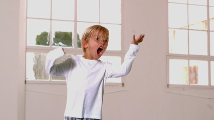 Boy in pajamas jumping and shouting in front of window