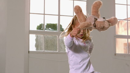 Girl in pajamas jumping and swinging teddy bear