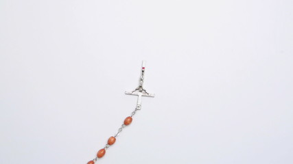 Crucifix of beads on white surface