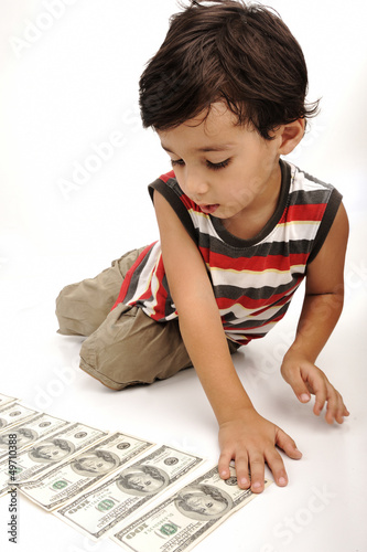 Cute little boy plays with money