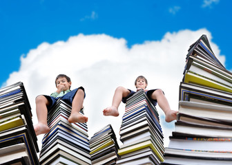Little boys sitting on large stack of books
