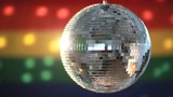 Disco ball spinning against rainbow flag