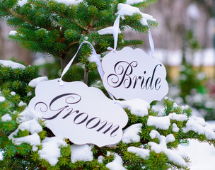 Bride and groom decoration boards handing on the fir-tree