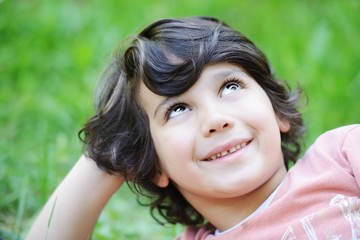 Closeup portrait of a little happy boy outside