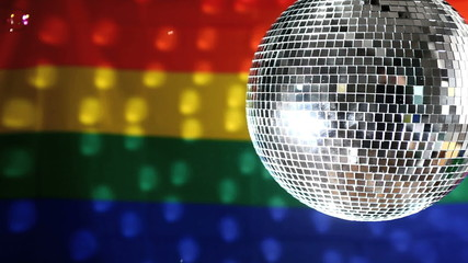 Disco ball revolving against gay pride flag
