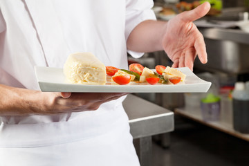 Chef Presenting Dish In Kitchen