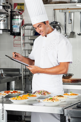 Young Chef With Clipboard At Kitchen