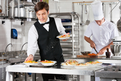 Leinwandbild Motiv Waiter And Chef Working In Commercial Kitchen