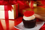 Cupcake with a red heart on top and gifts in boxes on red satin