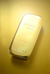 Goldbarren einzeln auf goldenem Untergrund mit Reflex