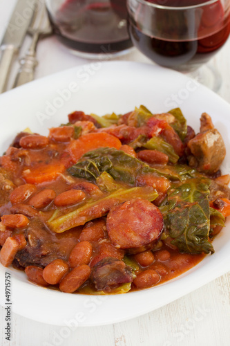 stew in the plate with glass of red wine