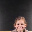 Fröhliches Mädchen vor Schultafel