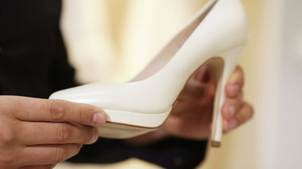 The groom takes his bride's shoes and twists