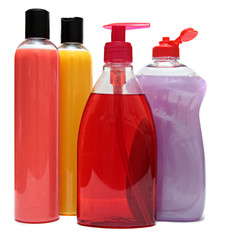 four colored plastic bottles with liquid soap and shower gel