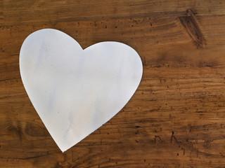 weißes Herz vor Holzwand