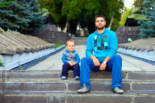 similar father and son sitting on the stairs in the park