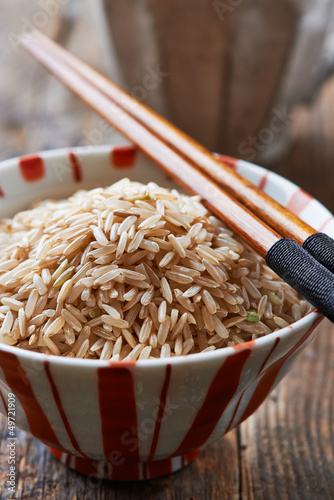 Bowl of  brown rice with chopsticks