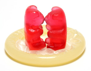 Red jelly figurine on a condom - birth control concept.