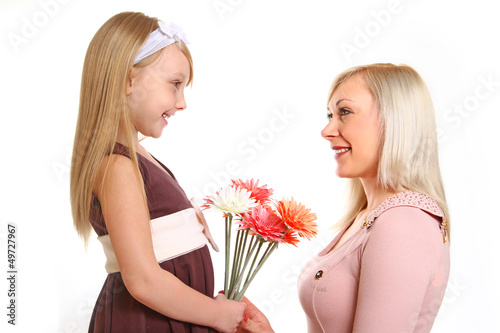 Daughter gives her mother flowers isolated on white background