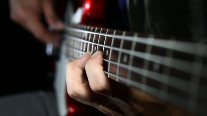 Bass guitar player close up playing virtuoso bass with fingers