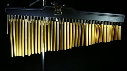 Super close up hand playing metallic gold chimes