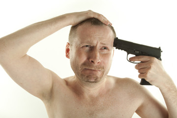 Young depressed man with pistol on white background