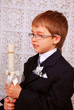boy with candle in day of the first holy communion