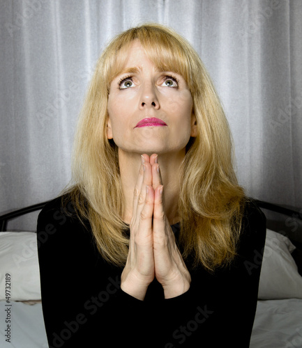 Depressed woman sits on bed praying