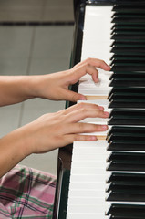 Close up of child's hands playing the piano..