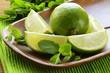 Fresh organic cut limes on wooden plate