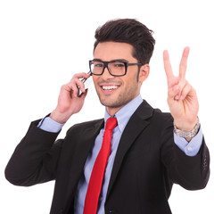 business man on phone shows victory sign