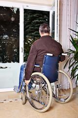 Mann sitzt im Rollstuhl und blickt aus dem Fenster