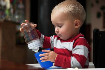 baby boy playing with bottle and mug indoor